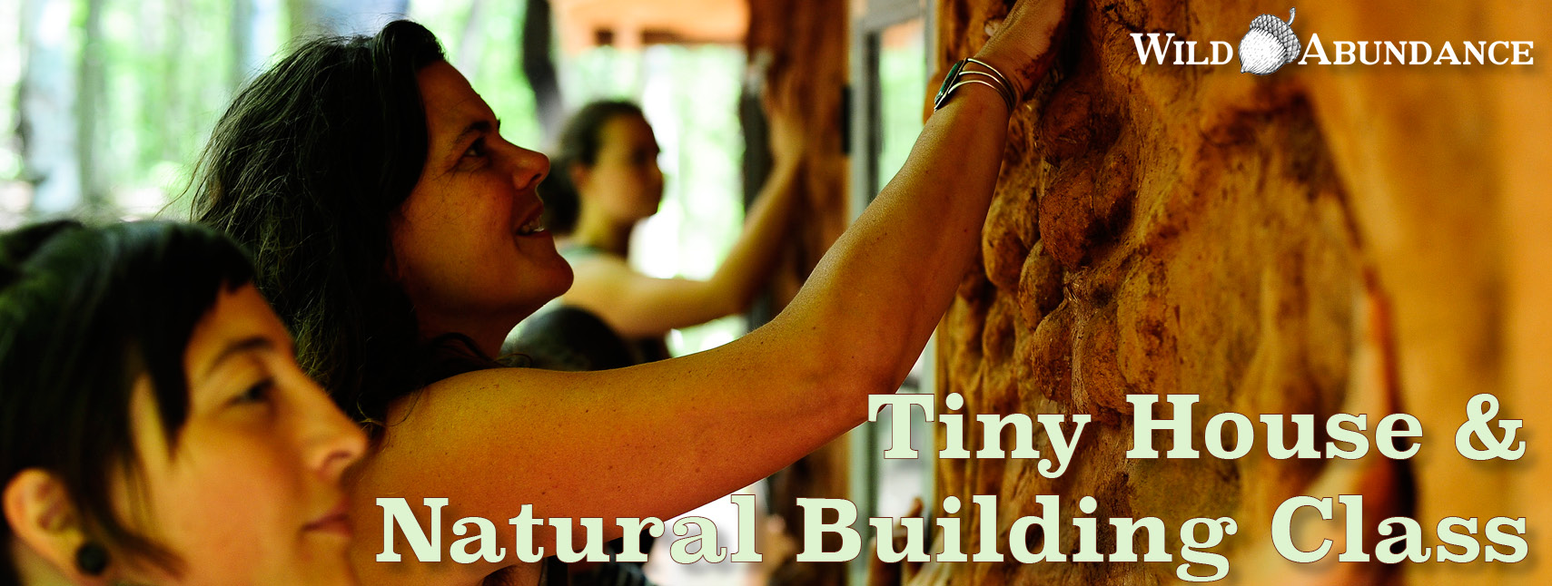 people applying natural plaster to an earthen wall in a natural building and tiny house course