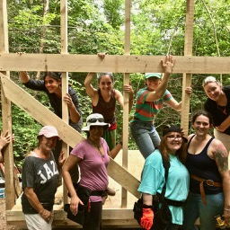 women carpenters building a structure raising a wall