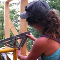 woman using a speed square to do carpentry