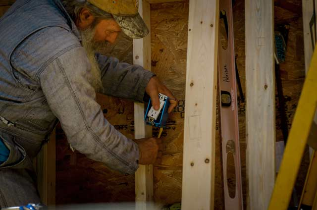 man installing an electrical outlet box in a tiny house