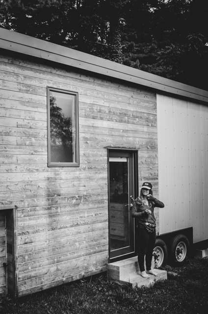 woman standing outside of a fancy tiny house on wheels