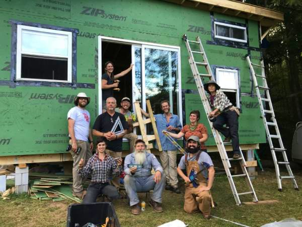 group of students participating in a tiny house workshop outside a tiny house