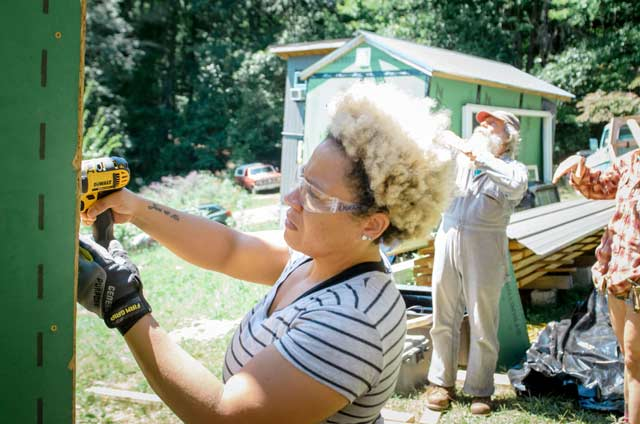 woman with an afro using an impact driver to build a tiny house