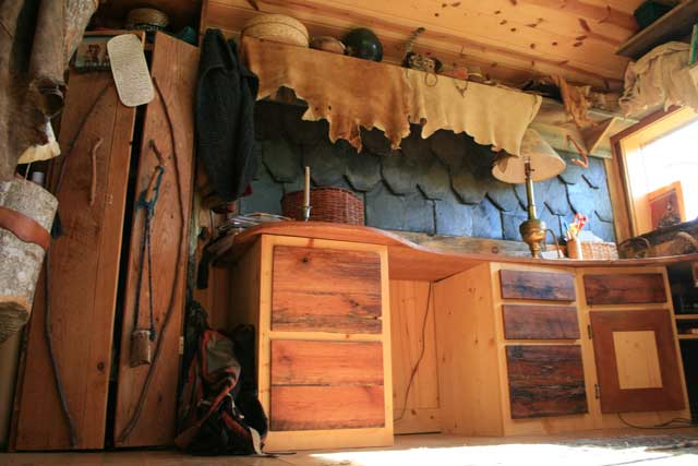 Inside of a handmade tiny house log cabin with cherry desk and slate shingles