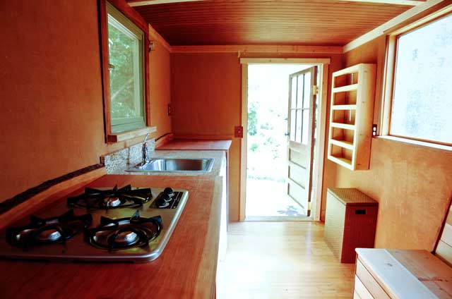 Interior of a tiny house built inside a box truck with natural clay paint