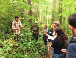 naturalist teaching about wild edible plants and mushrooms in the forest
