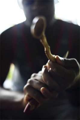 permaculture apprentice carving a spoon