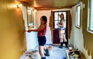 two women applying yellow DIY paint to drywall