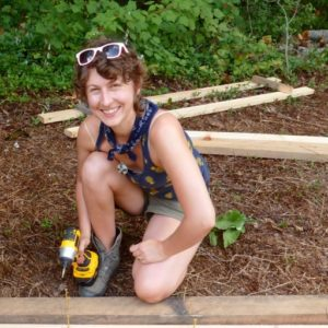 smiling female carpentry student Karen Shane with impact driver and lumber