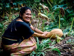 Permaculture Design Course student with squash in garden