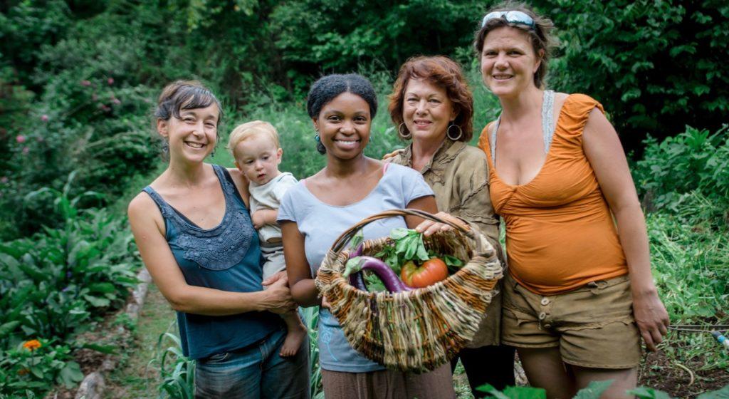women in garden with basket of vegetables