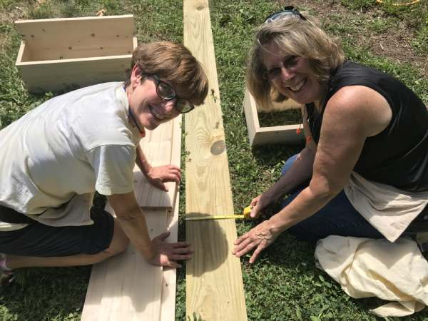 two women measuring a board in a home building workshop