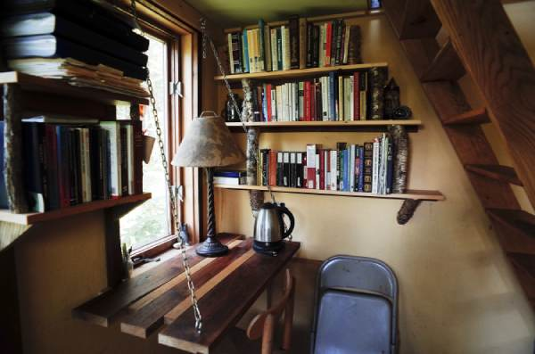 space efficient bookshelves and desk and ladder in tiny house