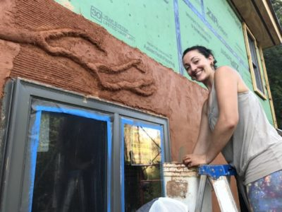 woman applying lime plaster to building