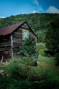 tall barn with painted design and green mountain