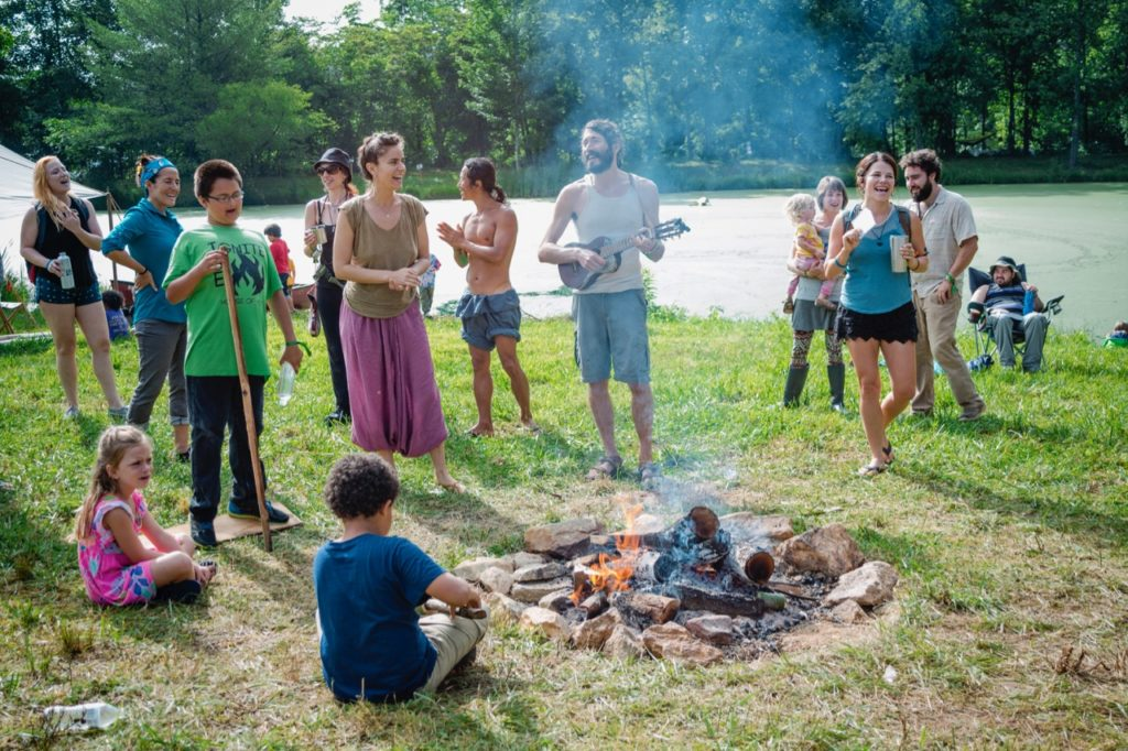 group of people singing around a fire including children