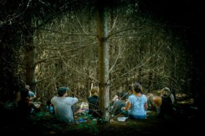 group of people in wilderness sitting at the base of a tree