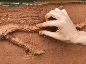 closeup of hand shaping cob in a natural building and permaculture design course