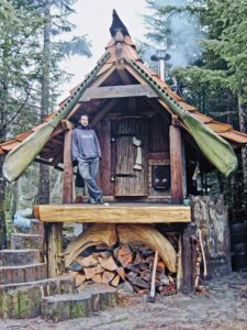beautiful natural artistic small tiny house with man on porch