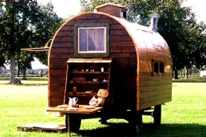 tiny arched hand built fishing cabin on wheels