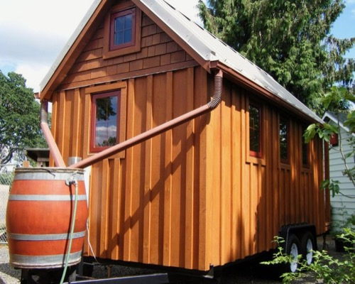 a tiny house with gutters and a rainwater catchment system including a rain barrel