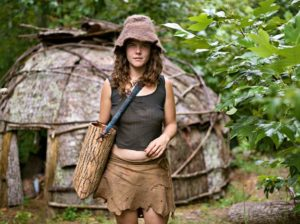 Natalie Bogwalker at the Wild Roots Community in front of a tulip poplar bark hut