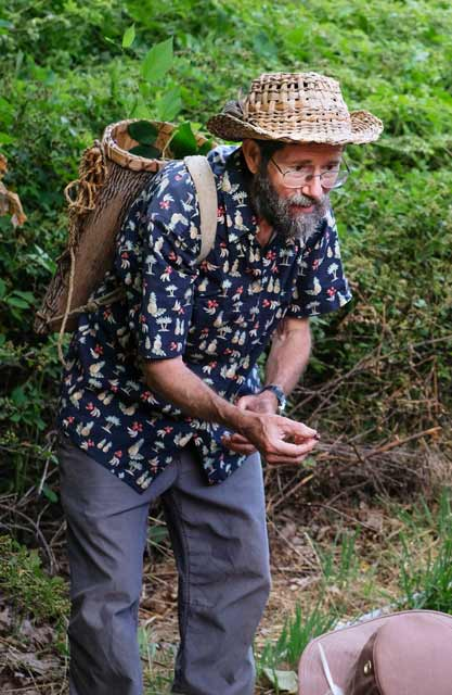 doug elliott with a tulip poplar bark pack basket and cattail hat teaching about wild edible plants