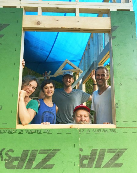 students looking out the window of a house under construction in a tiny house workshop