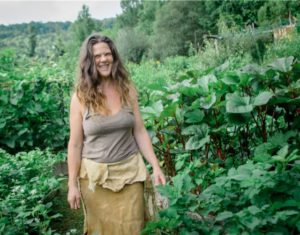 Natalie Bogwalker laughing in her garden next to okra plants