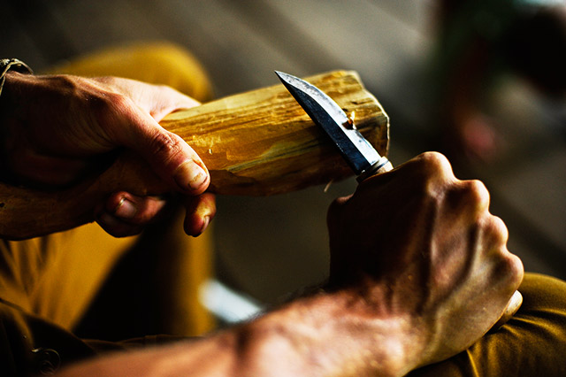 hands carving a wooden spoon with a knife