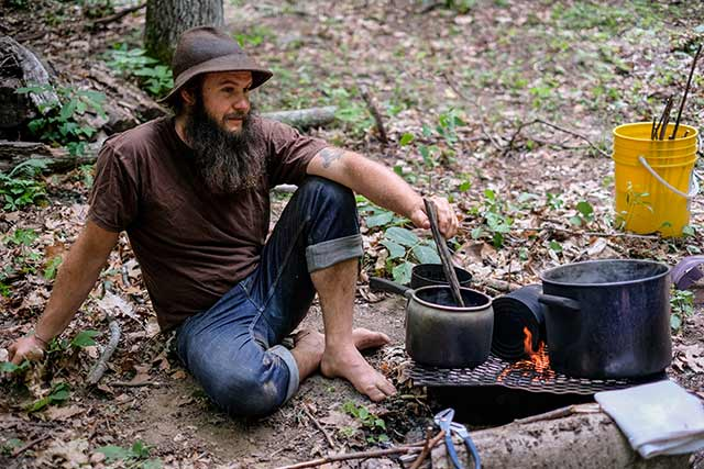 Man cooking over a campfire in a survival skills class