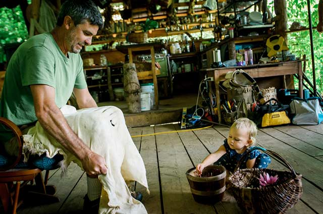 man stretching a deer hide during brain tanning with a little girl playing with a basket