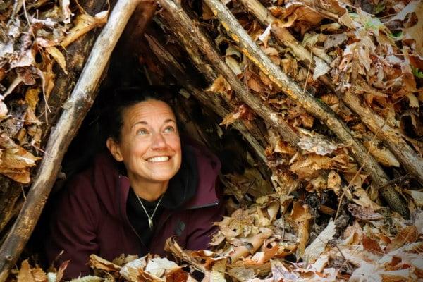 woman in leaf covered debris shelter