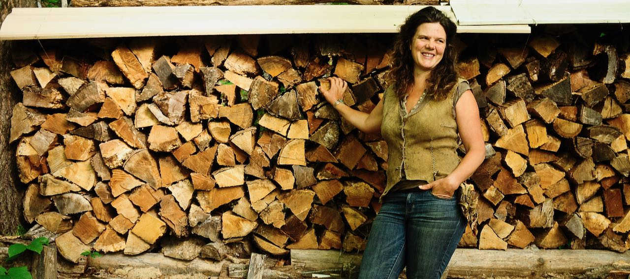 Natalie Bogwalker standing in front of a firewood stack at Wild Abundance