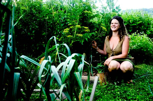 Natalie next to a garden bed with garlic