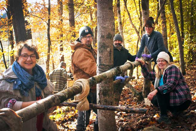 Group of brain tanning students wringing deer hides