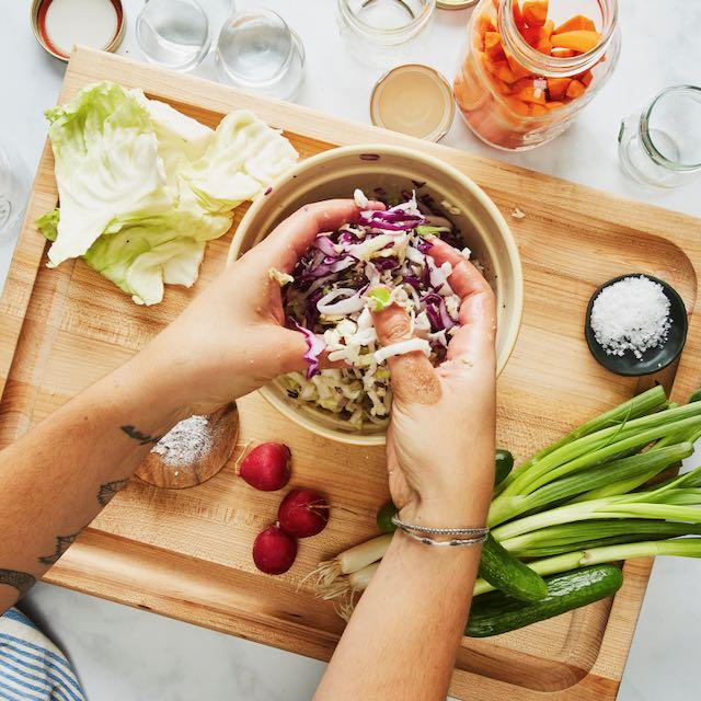 hands over crock making sauerkraut