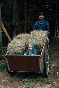 man with wagon load of hay and child in the wagon