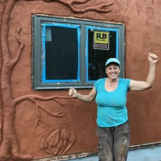 woman in front of tiny house with natural plaster