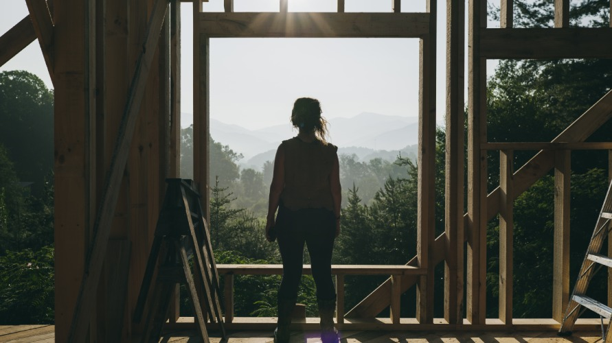 woman standing in front of rough window opening of tiny house