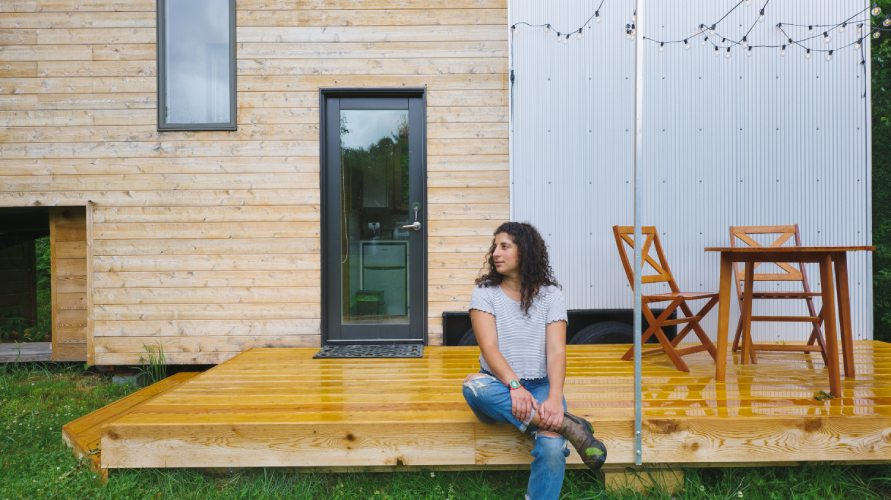 woman sitting on deck in front of tiny house on wheels