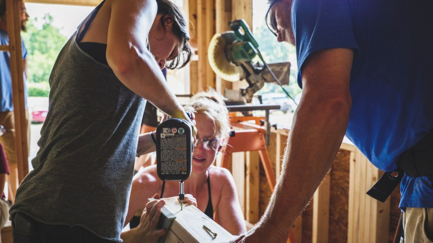tiny house class student using an impact driver to screw a board