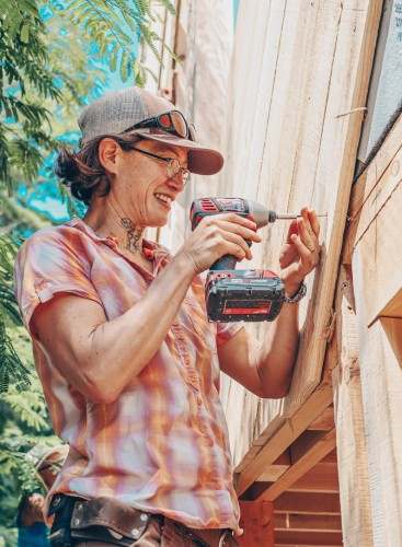 tiny house class student using impact driver to put up siding