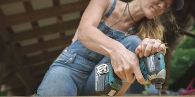 woman using impact driver to build tiny house