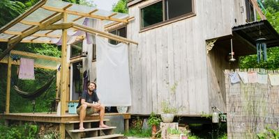 tiny house builder in front of his tiny house on wheels