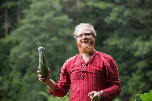 man holding up one zucchini