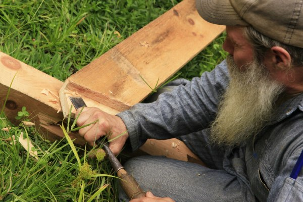 timber framing instructor using chisel to cut wood