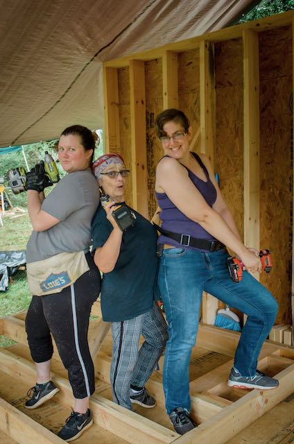 three women with tools doing carpentry