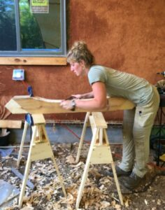 woman with a draw knife edging a timber