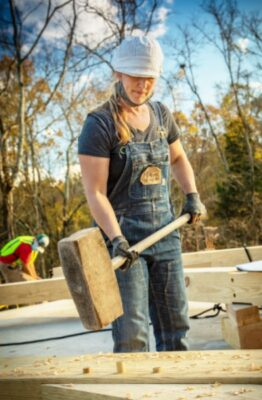 young woman with giant hammer building timber frame